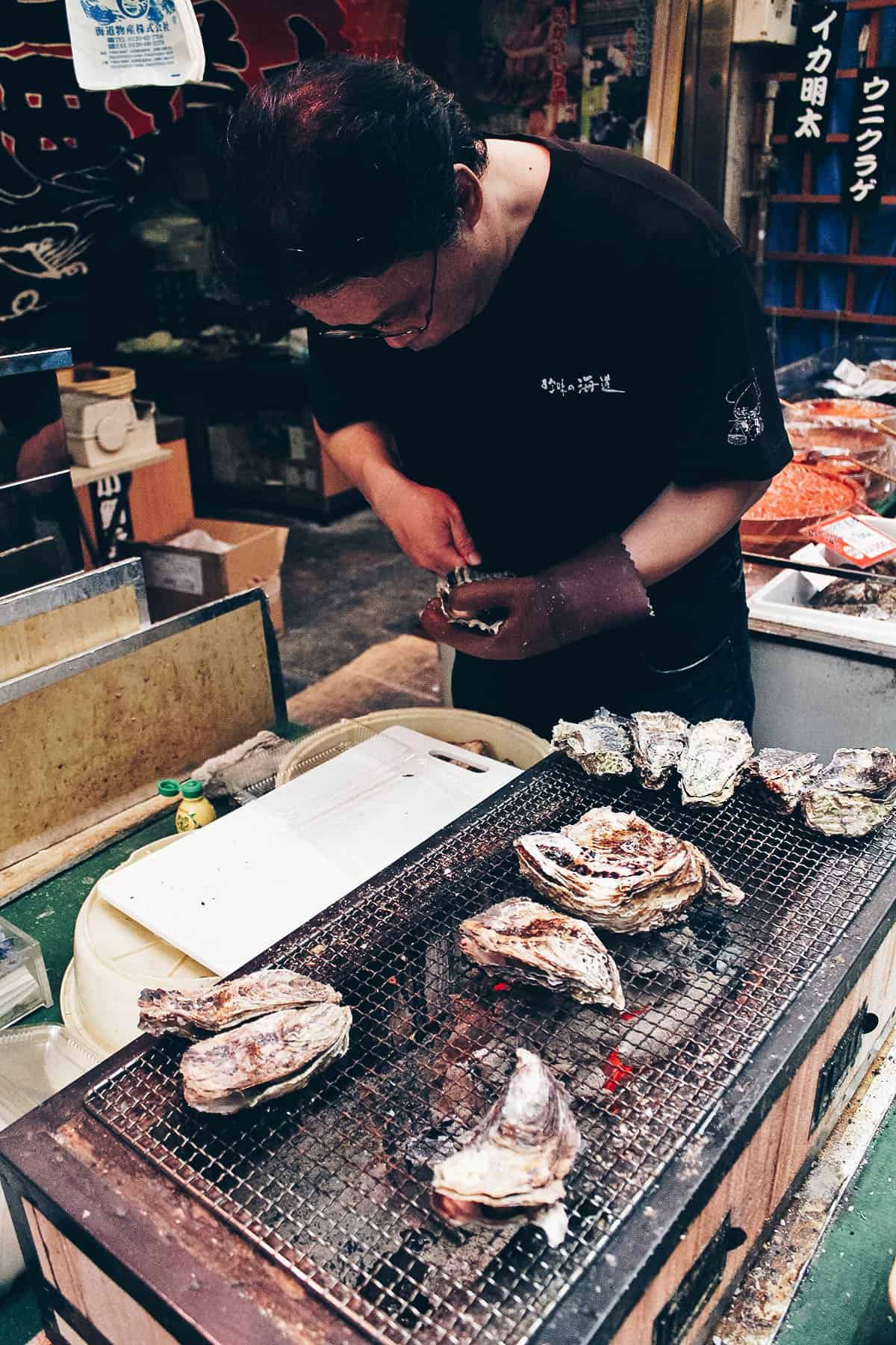 Man shucking oyster at Kuromon Ichiba Market