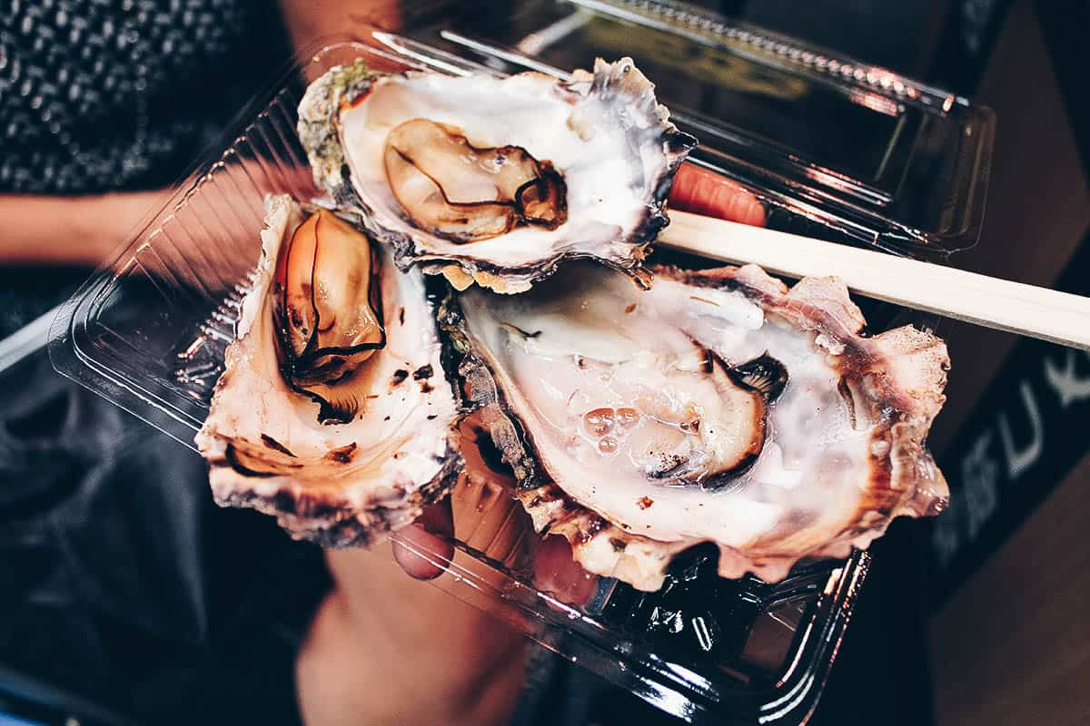 Grilling oysters at Kuromon Ichiba Market