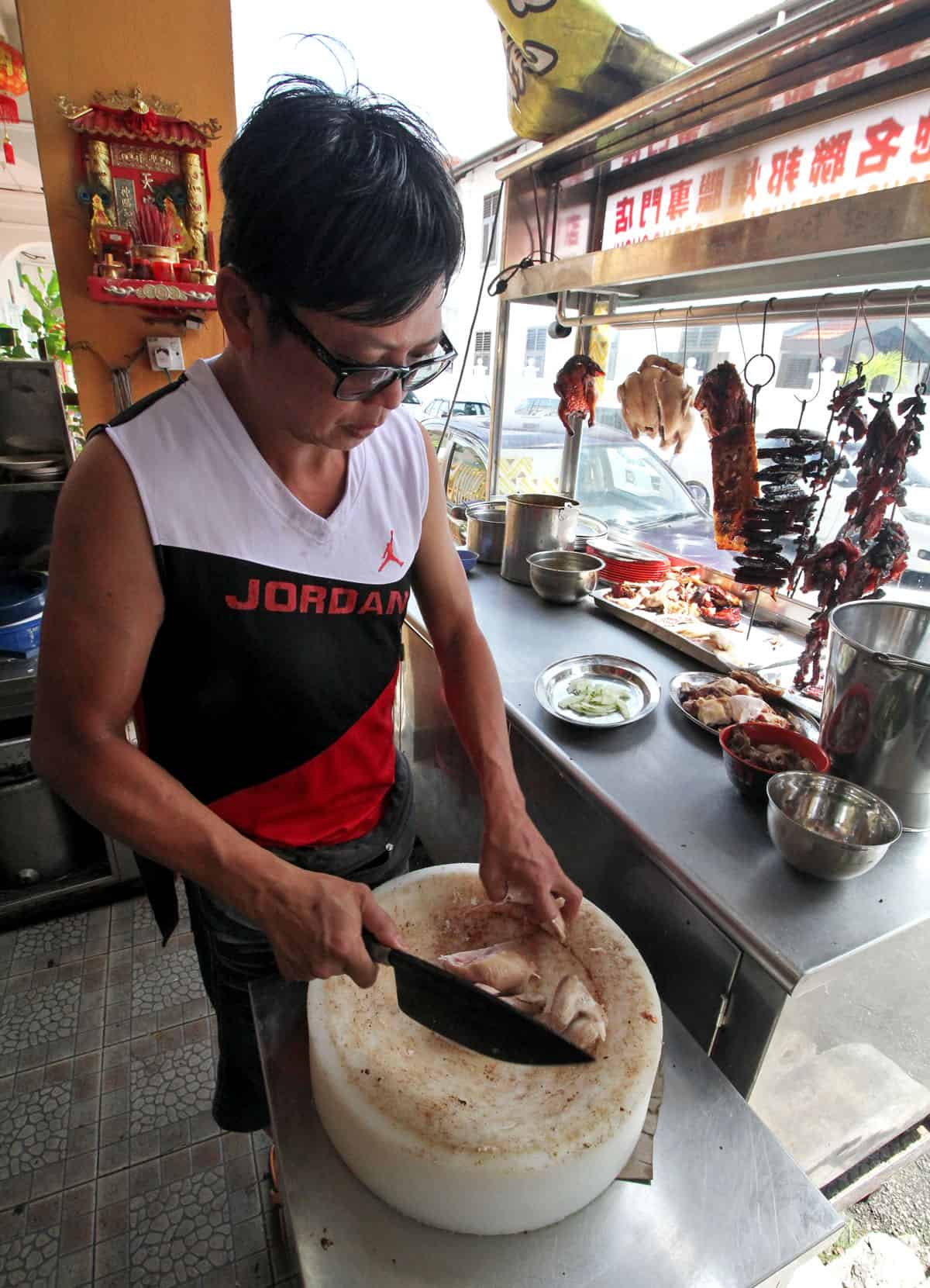 Chopping chicken at First Famous Federal Restaurant in Penang, Malaysia