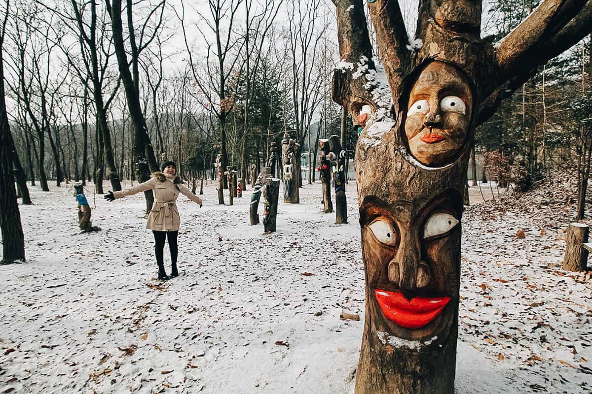 Carved faces on a tree at Nami Island