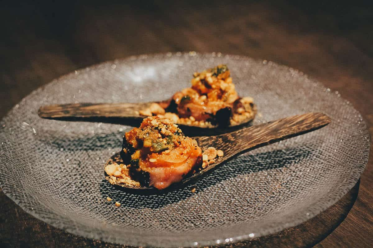 Charred octopus dish on wooden spoons