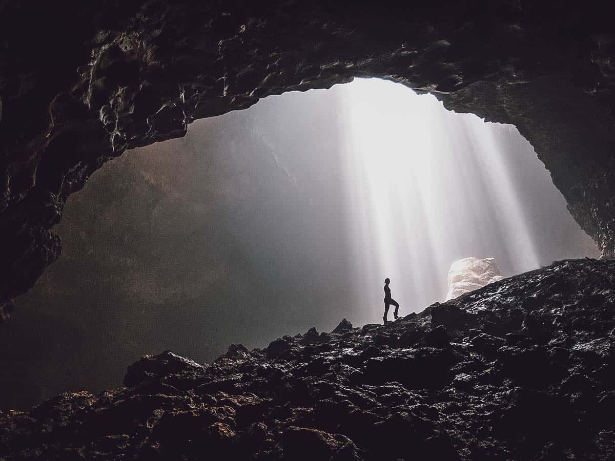 Person under light from hole in cave