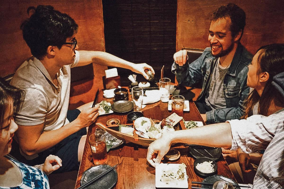 Tourists eating and drinking with their guide in Sapporo, Japan