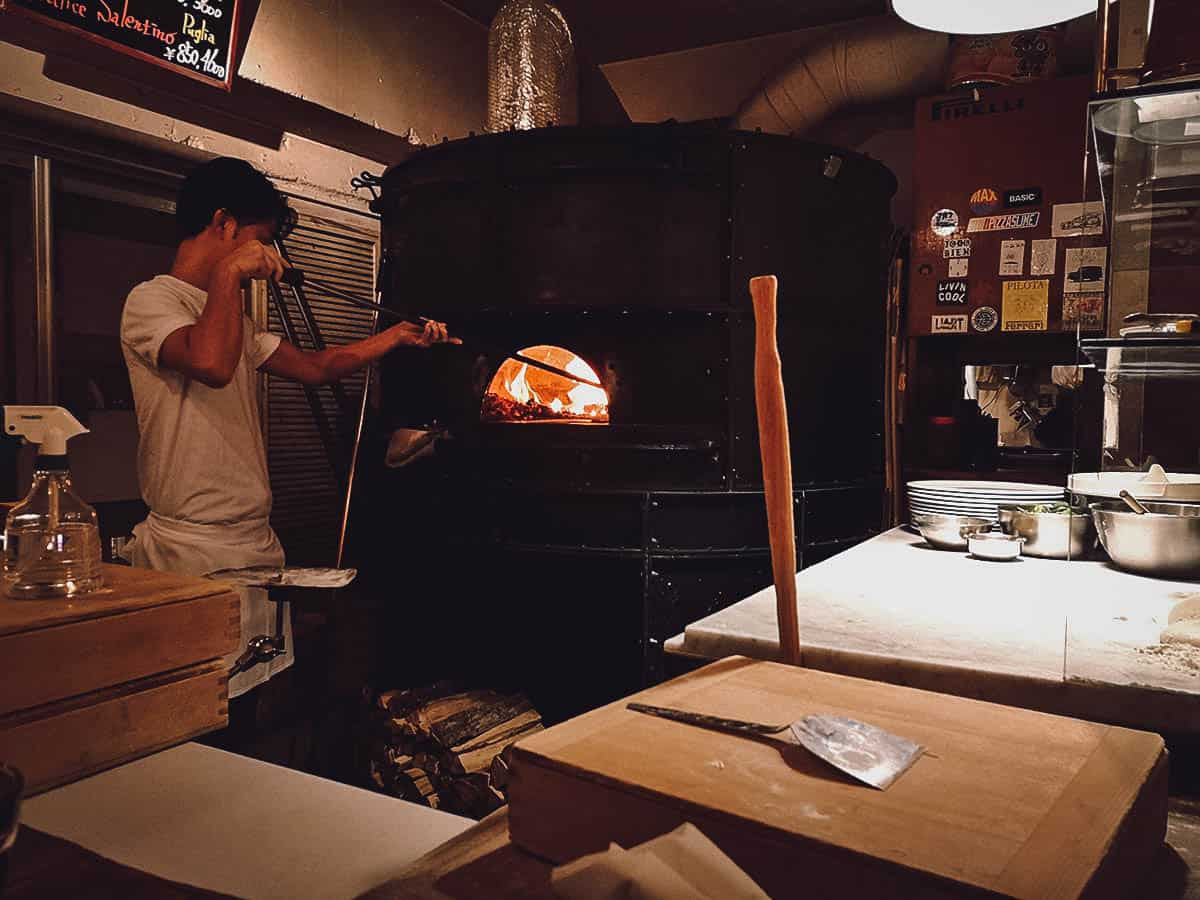 Putting pizza in the brick oven at Savoy in Tokyo, Japan