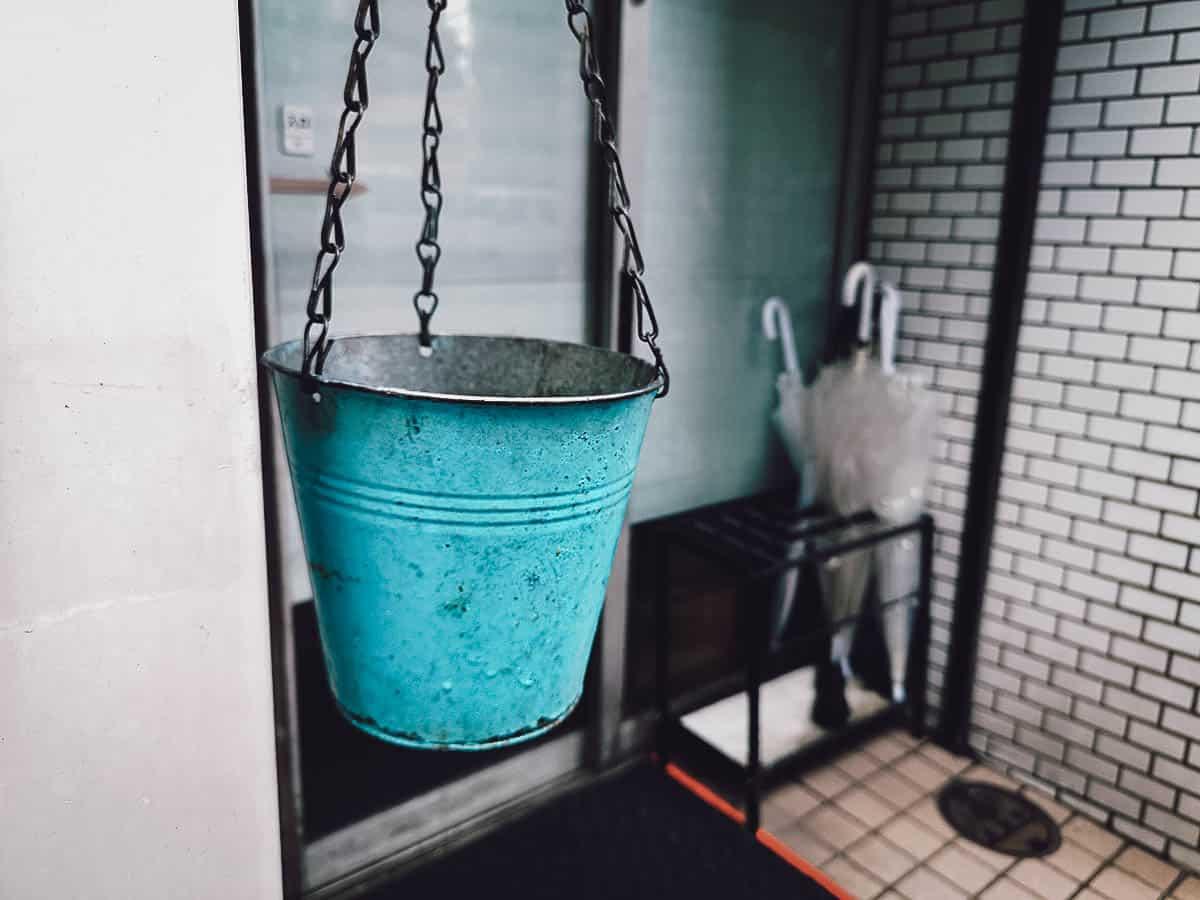 Blue bucket hanging outside Hakata Genki Ippai exterior in Fukuoka
