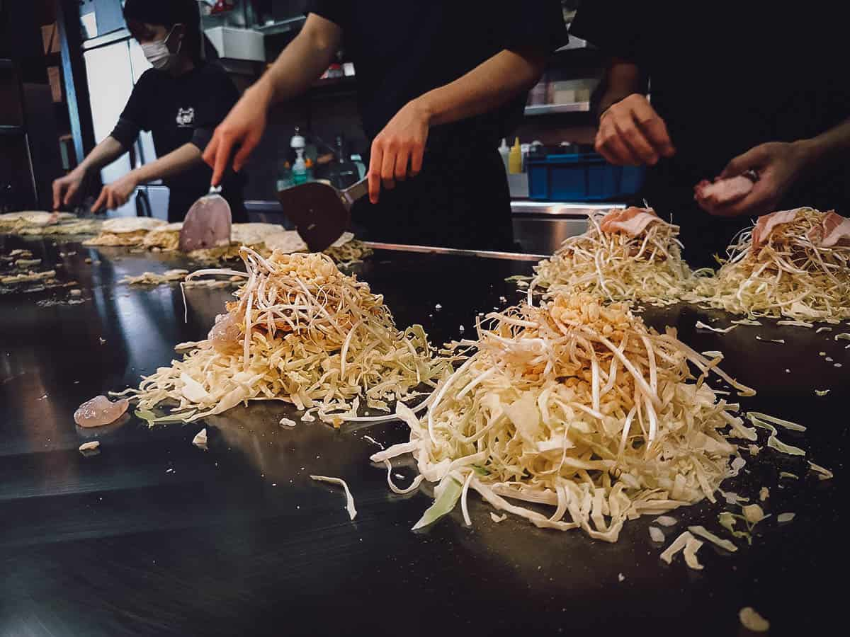 Cooks making okonomiyaki on a teppanyaki grill