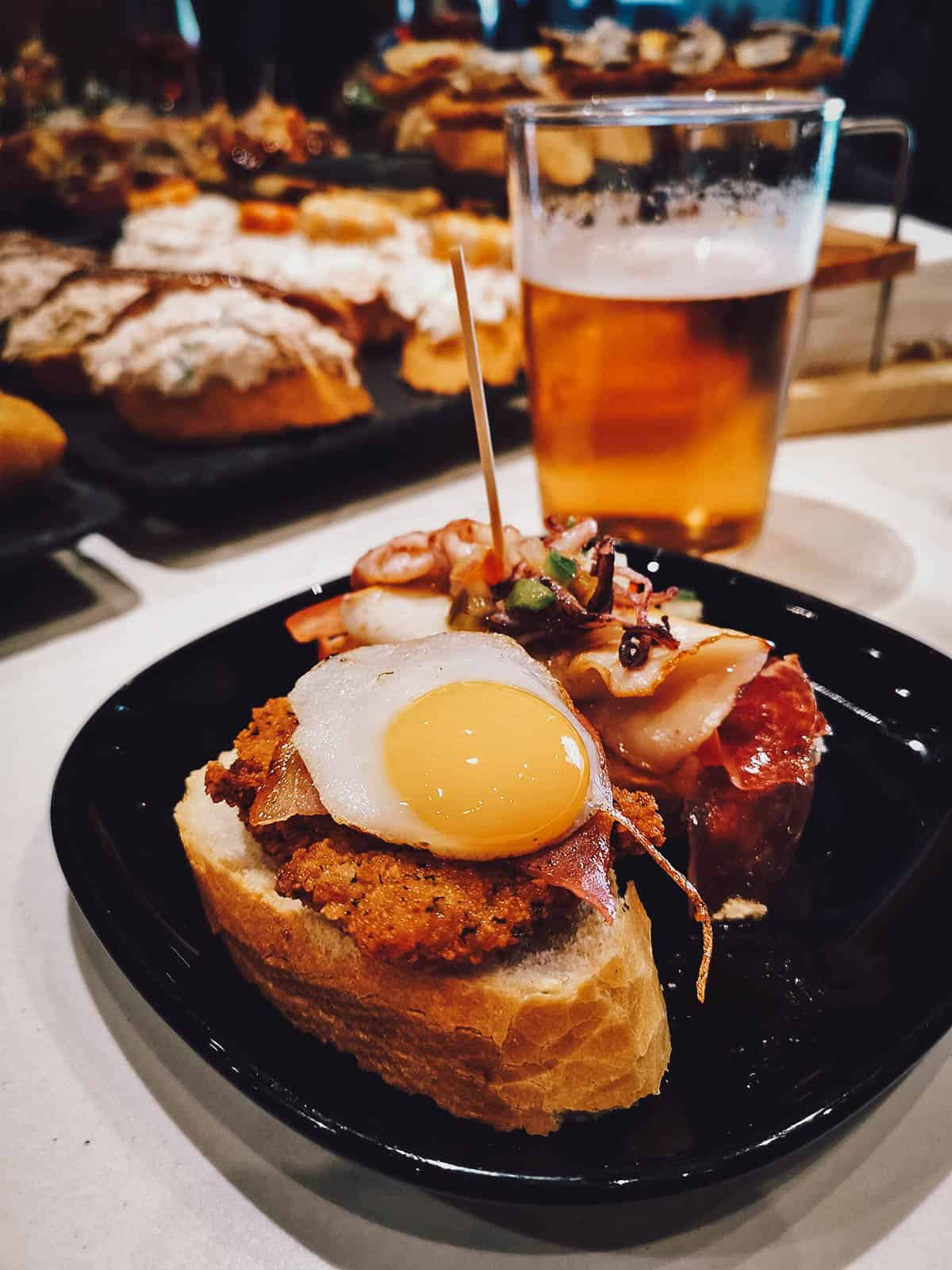 Pair of pintxos on a plate with beer