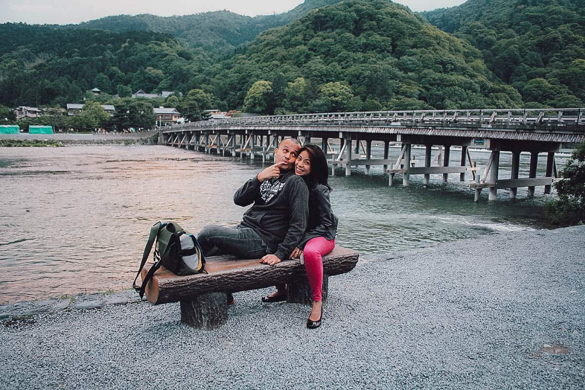 Man and woman on a bench with Togetsukyo Bridge in the background