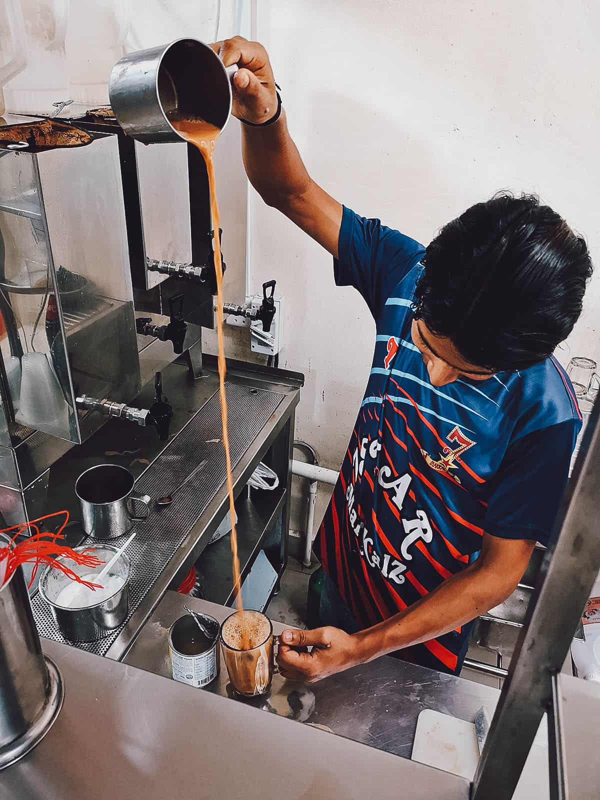 Pouring teh tarik in a glass in Singapore