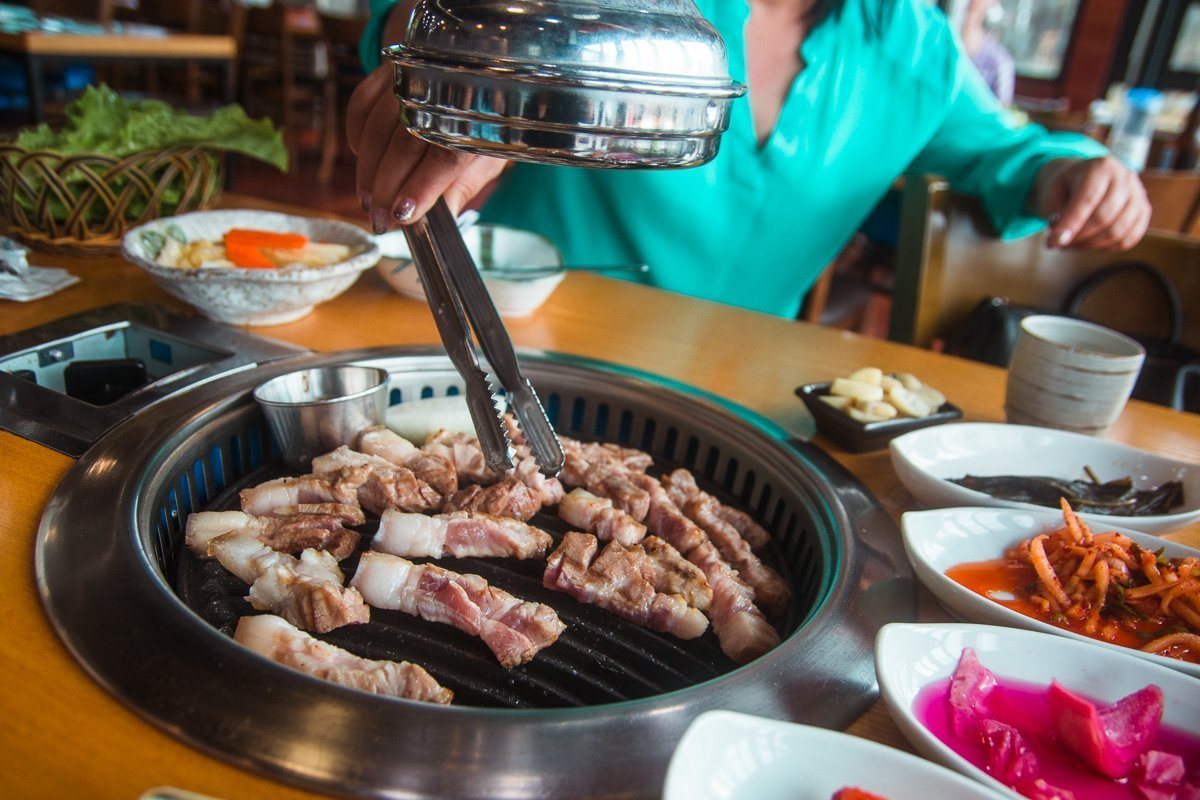 Woman grilling Jeju black pork