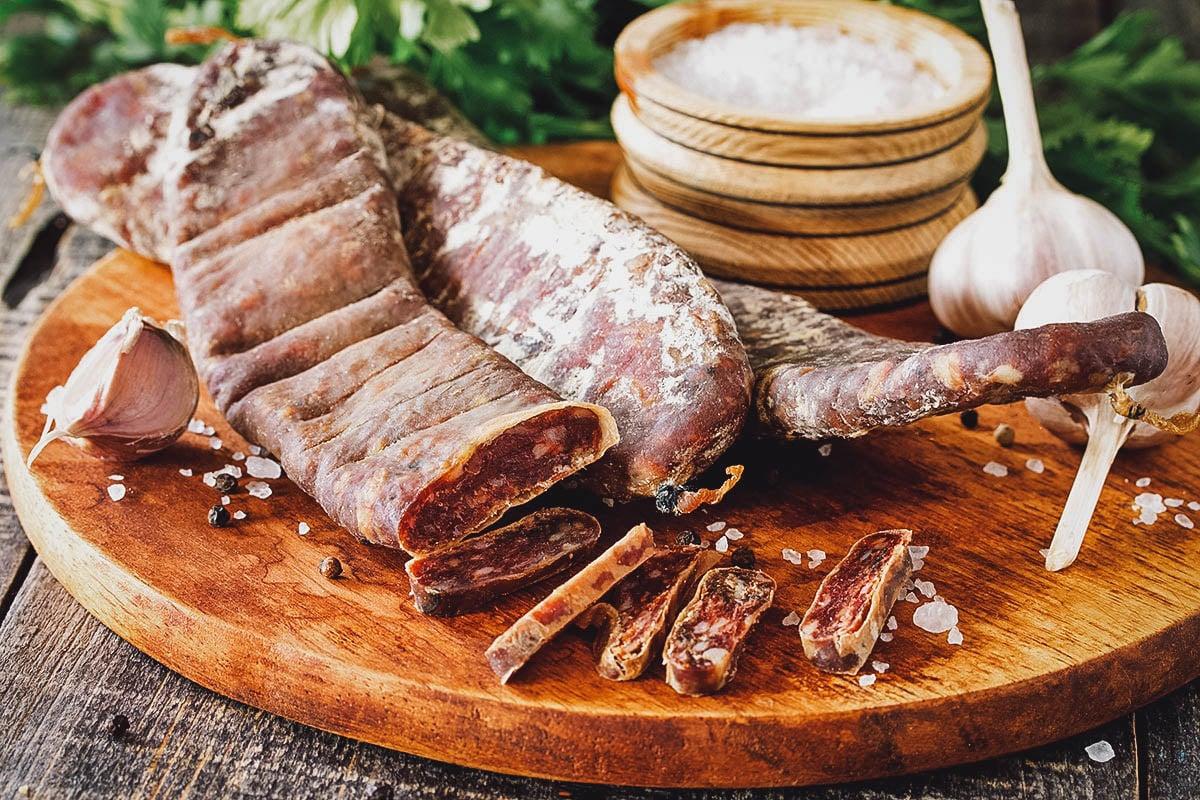 Sujuk on a chopping board with garlic and salt