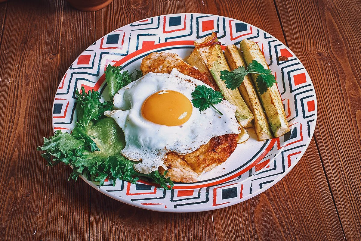Milanesa with fried eggs and french fries