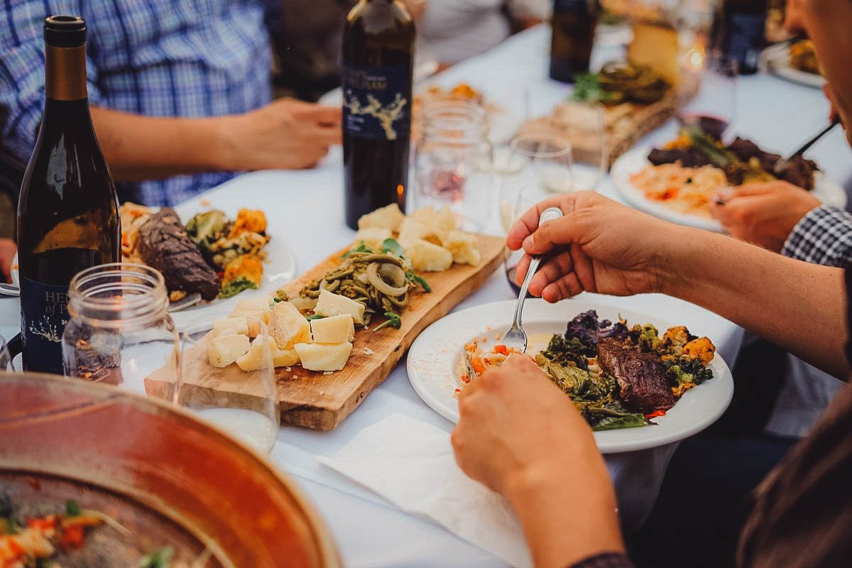 People enjoying a meal with wine