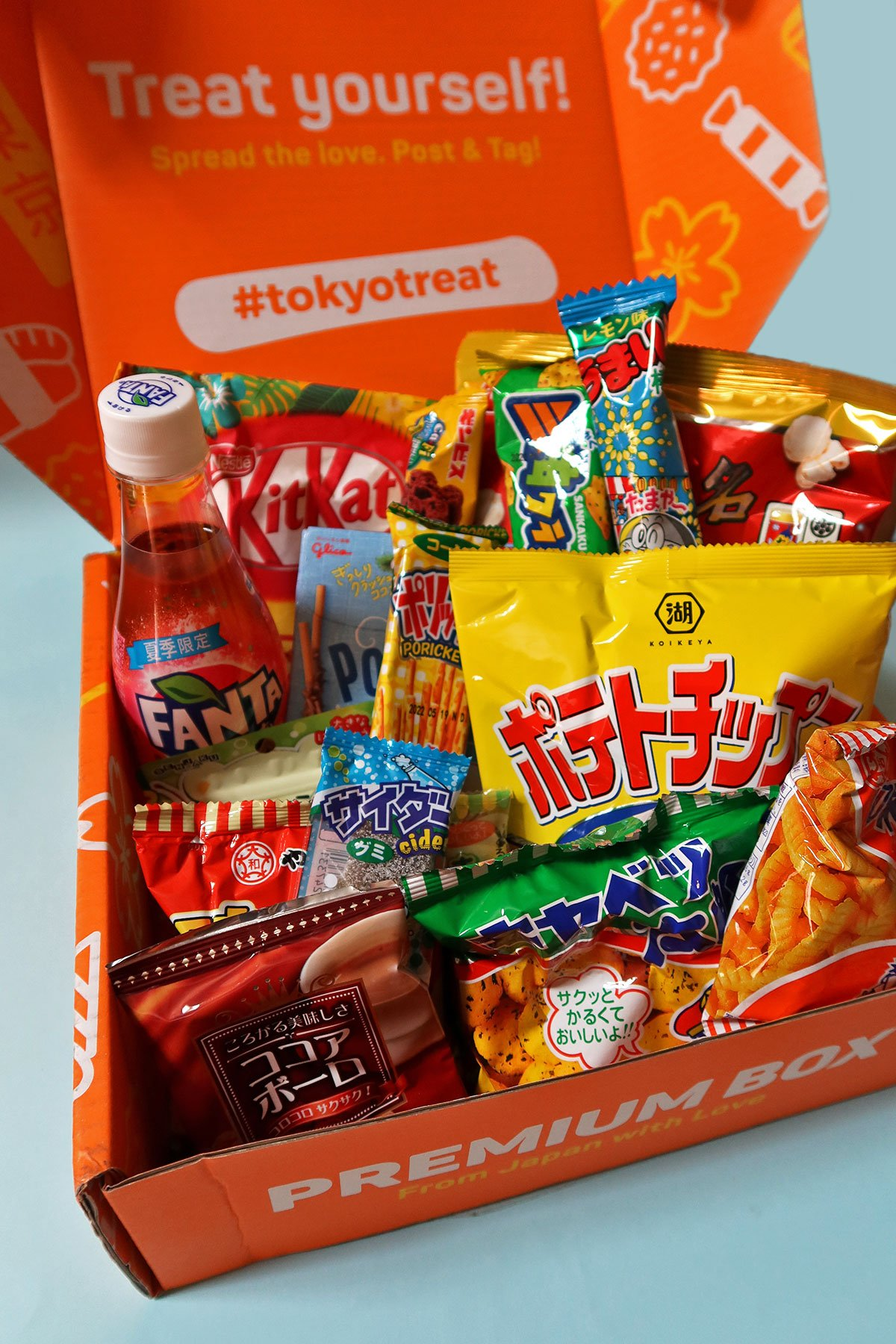 TokyoTreat's signature orange box loaded with Kit Kat bars, snack chips, party pack candies, drinks, DIY kits, etc