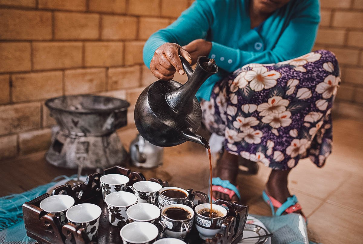 Woman pouring Ethiopian coffee in a dedicated coffee area