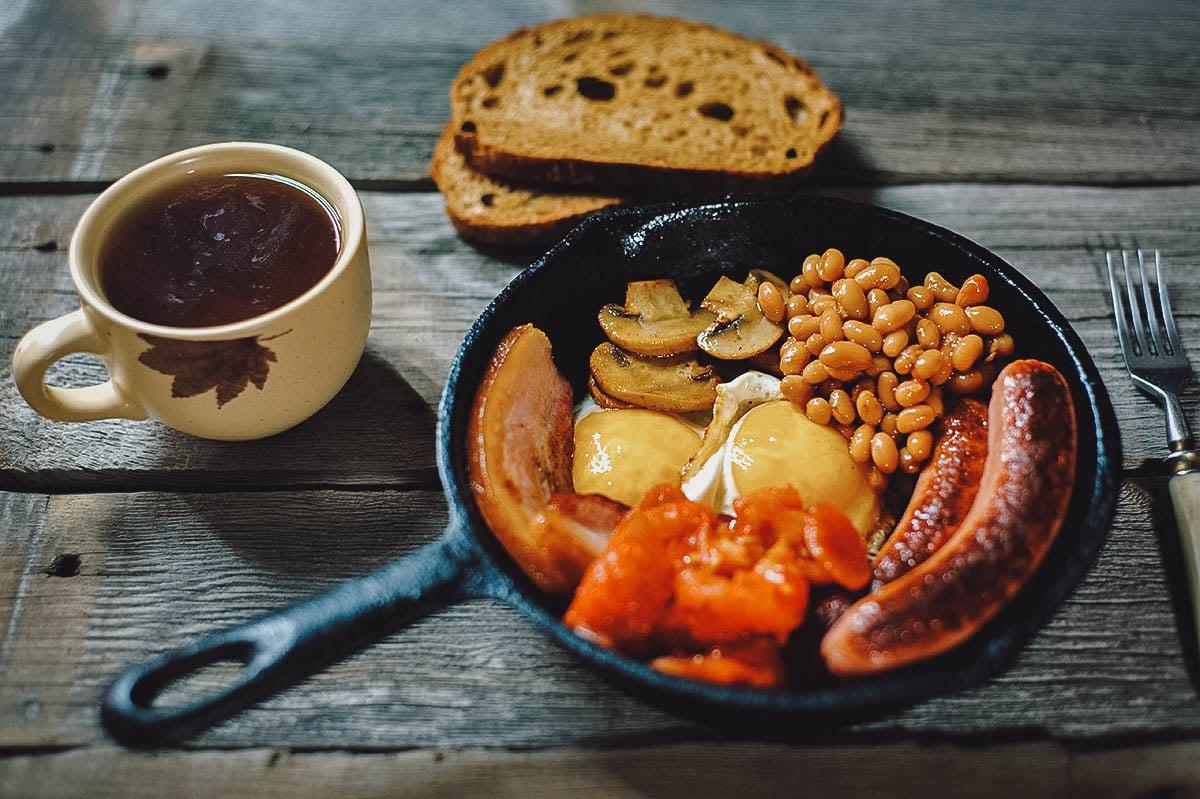Full Irish breakfast with black pudding, fried egg, tomatoes, mushrooms, baked beans, Irish bacon, Irish brown bread, potato bread, and Irish coffee