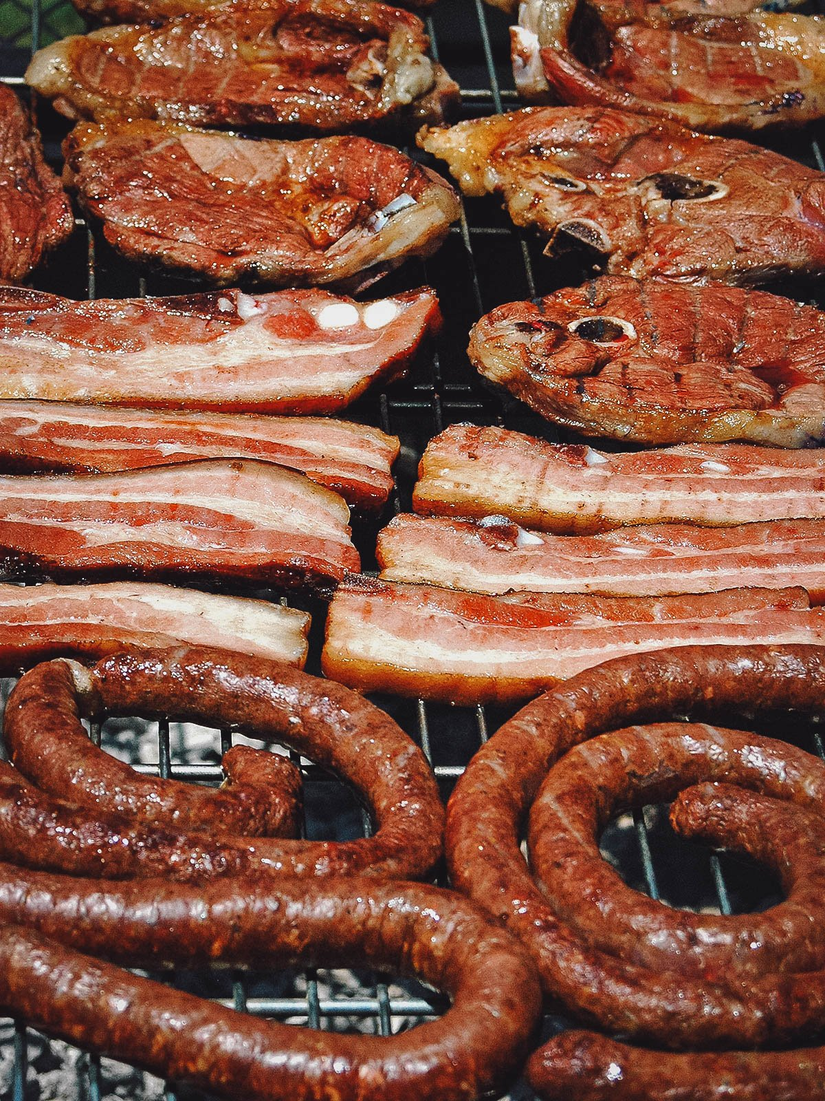 Different meats grilling at a braai or South African barbecue