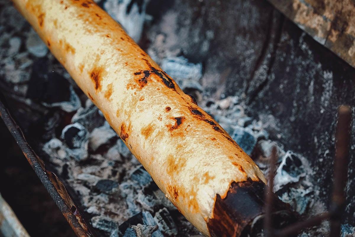 Chochoca roasting on a metal cylinder