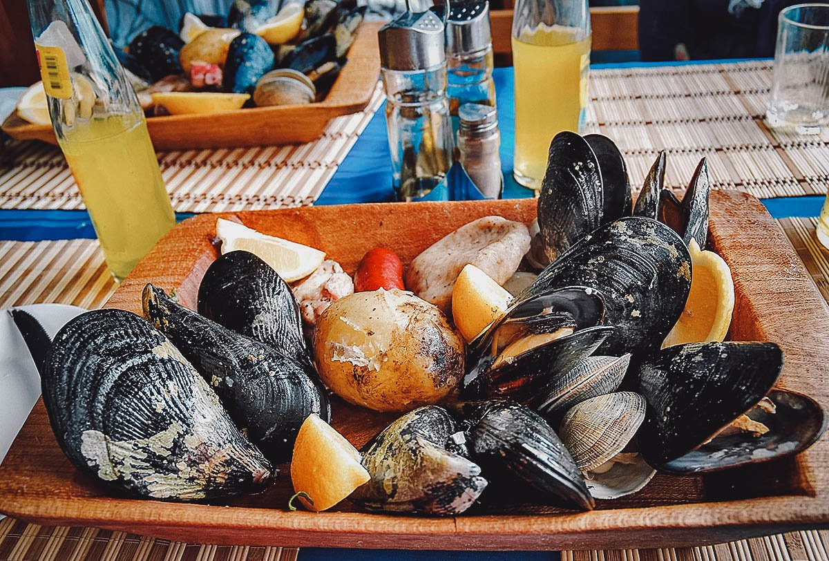 Curanto, a traditional seafood and meat dish served hot with lemon wedges